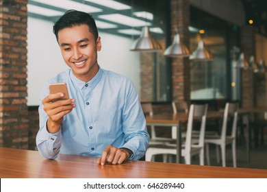 Smiling Asian Man Using Smartphone at Cafe Table