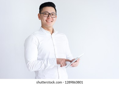 Smiling Asian man using tablet computer. Handsome young guy holding digital gadget. Technology concept. Isolated front view on white background.