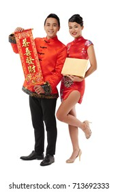 Smiling Asian man and woman presenting gift and scroll with couplets for Chinese New Year