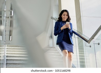 Smiling Asian manager in formalwear texting with friend on smartphone while going downstairs, portrait shot