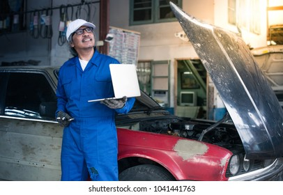Smiling asian mechanic in blue uniform holding laptop with car at the repair garage,