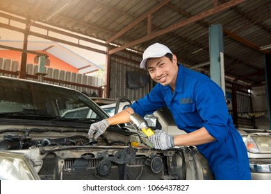 Smiling asian mechanic in blue uniform and white hat at the repair garage, holding lamp look at the camera