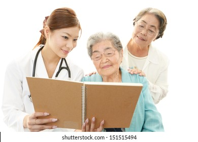 Smiling Asian medical doctor and old women