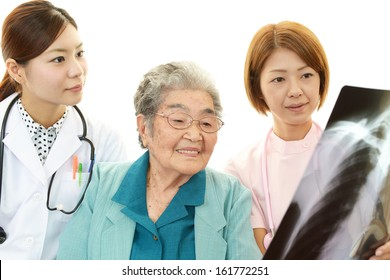 Smiling Asian medical staff with old woman
