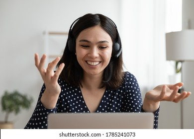 Smiling Asian millennial  headset talk speak on video call using computer at home. Happy Vietnamese young woman in headphones have webcam conference virtual event conversation on laptop online