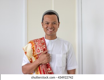 smiling asian muslim man bring prayer mat (sajadah)