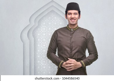 Smiling asian muslim man with cap and traditional dress in the mosque