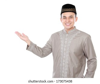 smiling asian muslim man presenting copy space isolated over white background