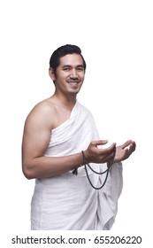 Smiling asian muslim man wearing ihram clothes with prayer beads isolated over white background