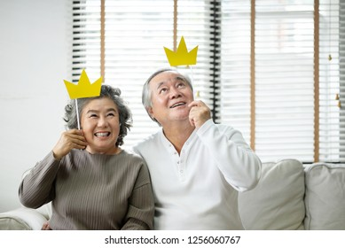 Smiling Asian Senior Couple holding yellow paper crowns on stick and looking up while sitting on couch together with copy space. Happiness, Funny, Laughing Feeling. Retirement.