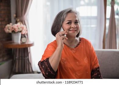Smiling asian senior woman using phone sitting on couch at home.