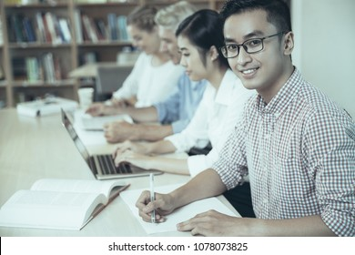 Smiling Asian student summarizing book in university library. Or young teacher in eyeglasses working in library and looking at camera. Education concept
