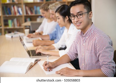 Smiling Asian student working in library