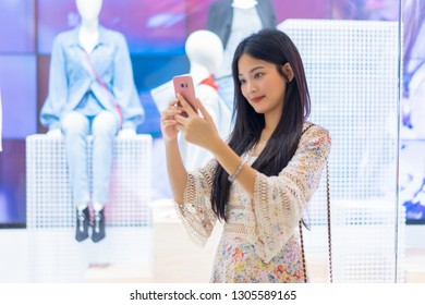 Smiling Asian Thai girl holding gift in shopping bags She Compares prices on mobile smartphone looking for clothes in a dress shop  - Concepts of relaxing lifestyle,shopping online technology in city