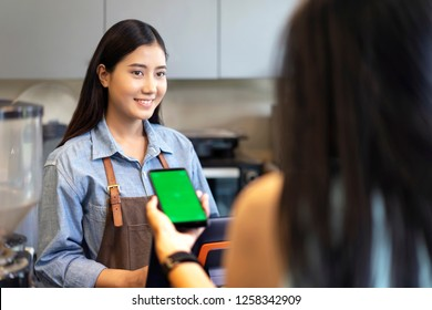 Smiling asian waiter prepares the bill on computer tablet, Customer using her smartphone and nfs high technology to pay a barista for her purchase with phone, transaction and mobile payment online.