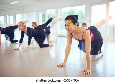 Smiling Asian and white adult ballet dancers standing and doing gymnastics in ballet class.