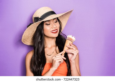 ac56019072 smiling asian woman in beach attire holding an ice-cream cone in her hands  and