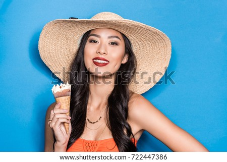 39235f34f6 smiling asian woman in beach attire holding an ice-cream cone and looking  at camera