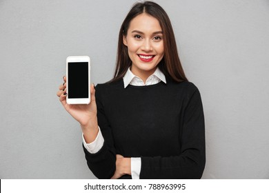 Smiling asian woman in business clothes showing blank smartphone screen while looking at the camera over gray background