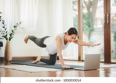 Lächelnd asiatische Frau, die einen Arm ein Bein macht, planken, um die Kernmuskulatur im Online-Training von Laptop zu Hause im Wohnzimmer auszuüben. Selbstisolierung und Training zu Hause während COVID-19.