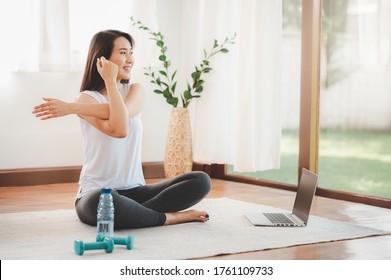 Lächelnde Asiatin, die Yoga-Schulter, die sich auf der Online-Klasse von Laptop zu Hause im Wohnzimmer. Selbstisolierung und Training zu Hause während COVID-19.