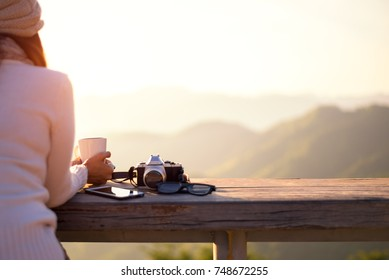Smiling asian Woman drinking coffee and tea and take a photo and relax in sun sitting outdoor in sunshine light enjoy relax her warm morning at balcony house, vintage. Lifestyle Concept