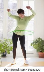 Smiling Asian woman exercising with hula hoop