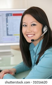 Smiling Asian woman with headset and computer monitor