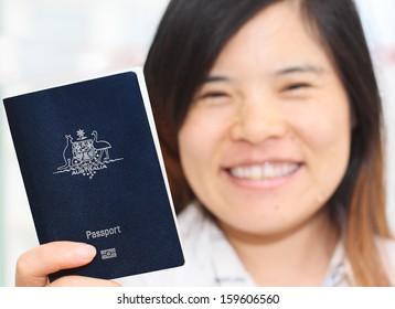 Smiling Asian Woman Holding an Australian Passport in narrow focus