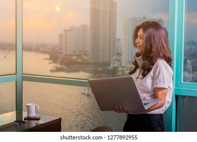 Smiling asian woman with Laptop Working, Planning, Thinking standing in front of windows in an office building overlooking the city and river. Copy space