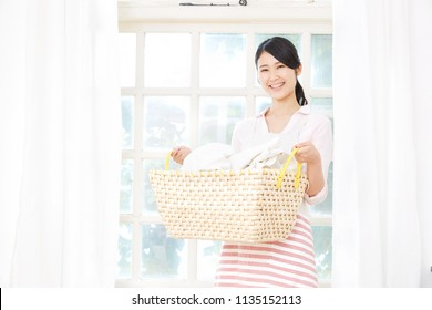 smiling Asian woman with the laundry
