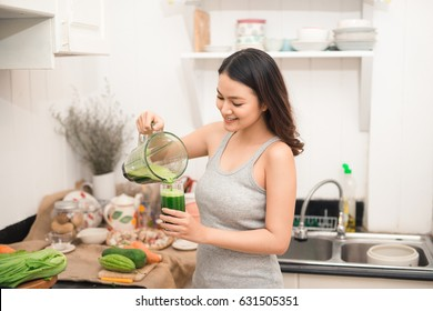 Smiling asian woman making smoothie with fresh vegetables in the blender in kitchen at home.