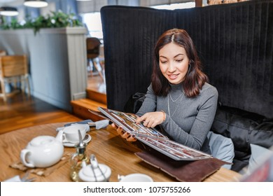A smiling asian woman in a restaurant reading menu and chooses among different cuisines