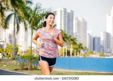 Smiling Asian woman running. Skyscrapers on a background