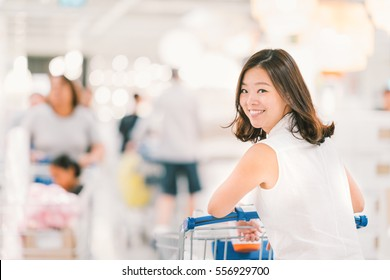 Smiling Asian woman with shopping cart or trolley at department store or shopping mall, happy lifestyle or shopaholic concept, blur bokeh background with crowd and copy space