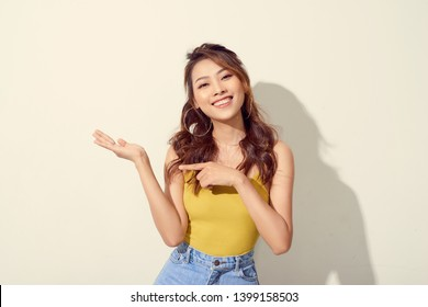 Smiling asian woman showing open hand palm to to the copy space for product or something