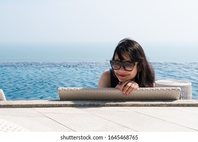 Smiling  asian woman sitting backward on a wicker daybed near swimming pool