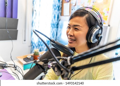 Smiling asian woman Speaks to Microphones, Broadcasting Program on Air. Freelance and technology concept