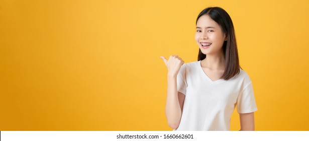 Smiling Asian woman stand and pointing finger on orange background.