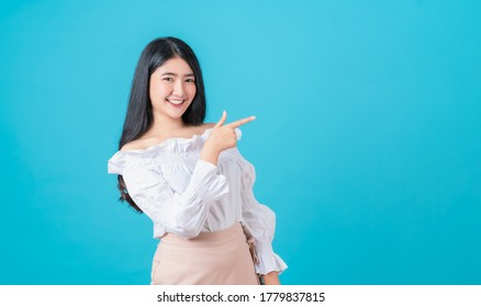 Smiling Asian woman stand and pointing finger on blue background.