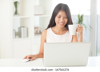 Smiling Asian woman surfing the Internet at home.