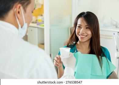 Lächelende Asianerin nimmt ein Glas Wasser von ihrem Zahnarzt