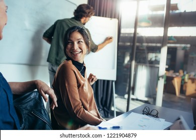 Smiling asian woman talking with coworker sitting by in business presentation. Business presentation in modern office board room.