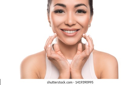 Smiling asian woman touching here face by hands and looking at camera. isolated on white background. Skin care and natural beauty concept.