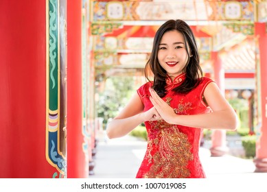 Smiling Asian woman in traditional red cheongsam qipao dress making salute