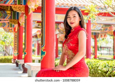 Smiling Asian woman in traditional red cheongsam qipao dress sitting with hands resting on lap in beautiful Chinese temple