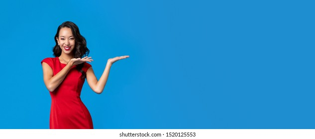 Smiling Asian woman wearing red dress doing presenting gesture with open hands isolated on blue banner background with copy space