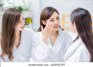 Smiling asian women apply cream on her face and feel good