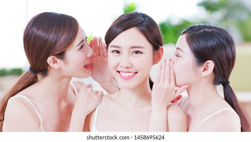 Smiling asian women friend talk to the person at the middle