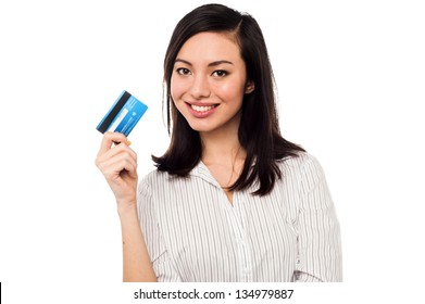 Smiling asian young female model holding up credit card.